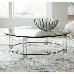 A chrome ring frame, clear glass and acrylic combine to create this chic, contemporary round cocktail table that instantly elevates living room decor. wide x high. Design by Bassett Mirror Company. Style # at Lamps Plus. Living Room Lighting Tips, Living Room Decor, Couch With Chaise, Bubble Chandelier, Desk With Drawers, Cocktail Tables, The Ordinary, A Table, Chrome