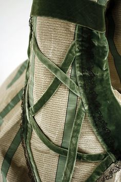 Detail of striped silk dress, American or European, ca 1858-1863. Velvet ribbons in lattice fashion over sleeves. MET