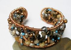 "Wire and beads combine to make a stunning ""Bead Soup Bangle"" designed by Eva Sherman."
