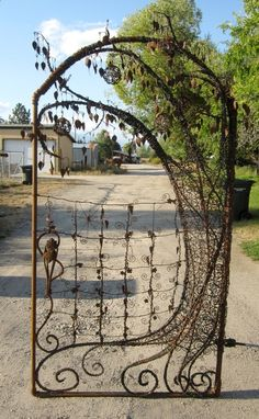 Unique garden gate using metal pipe, re bar, old fencing, barbed wire, metal table legs, rusty tin cans and vintage chandelier crystals