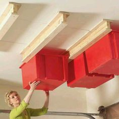 DIY STORAGE IDEA.... A chunk of plywood cut into strips, a couple pieces of 2x4 and a few screws... that's all it takes to turn overhead space into organized storage.