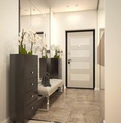 Peindre un couloir - la porte d'entrée est fermée, un placard noir avec une orchidée blanche est appuyé sur le mur.