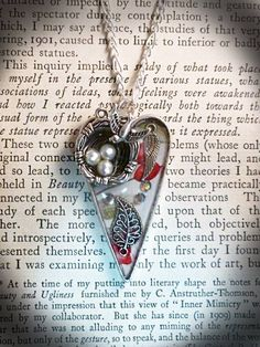"""Avialae Pendant - Large heart-shaped pendant with a silver plated bird, perched upon its nest looking down at it' three pearlised eggs, set in resin with filigree and engraved silver wings. Size - 4cm x 3cm, comes on a silver plated chain with a small matching wing at the end of the extender chain, length - 18"""" - 20"""". Price - £18.99. p&p - £2.99."""
