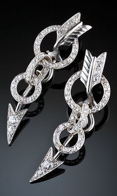 A pair of Art Deco diamond and white gold arrow ear cuffs, American, 1930s. Each ear cuff designed as an arrow piercing two targets, set with diamonds and mounted in 18k white gold. The earrings curve up the ears when worn. #ArtDeco #EarCuffs