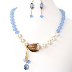 Charlotte: Blue Floral Necklace Set. This ensemble features semi-precious quartz with Swarovski pearls. It's floral accent is carved brass with Swarovski crystal dangle pendants. SOLD