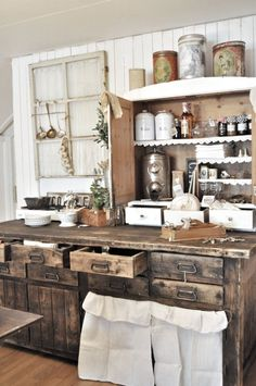 Farmhouse Kitchen..with brown wood cabinets...love the curtains under the cabinets & the old window on the wall.