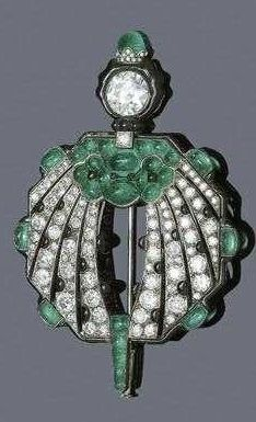 DIAMOND, EMERALD, ONYX AND ENAMEL BROOCH, France, ca. 1925. Very fine octagonal open-worked Art Deco brooch in the shape of a stylised bird, with black enamelled rim, set with emerald cabochons, old mine-, single- and rose-cut diamonds and onyx cabochons. Numbered and with platinum and gold mark.