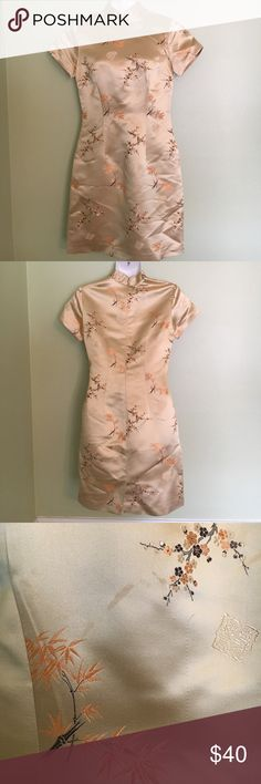 """Hugo Buscati Vintage Pin-Up Style Asian Dress Pre-loved, very well cared for kimono style dress featuring a glowing gold hue with 73% rayon, 27% silk material. Originally purchased from Victoria's Secret   Japanese cherry blossom detailing, with a high collar & a perfect curvy cut.   Hidden zipper in the rear & fully lined with 100% acetate, a polyester satin and approximately 33"""" in total length   Minor defect on the front as photographed, & is minimally noticed.   Dress comes from a clean…"""