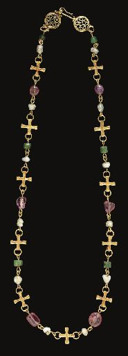 A NECKLACE OF ELEVEN BYZANTINE GOLD CROSSES   CIRCA 7TH CENTURY A.D.   Each originally part of a necklace, now strung with both ancient and modern beads, including twelve pearl beads, six irregularly shaped pink tourmaline beads, and six faceted cylindrical green chalcedony beads, terminating in openwork disks with volutes, topped with a hook-and-loop closure, the edges ribbed, granulation at the join