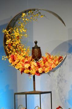 Création florale dans les tons jaune et orange autour d'une urne