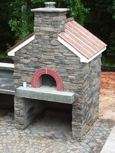 Description: An outdoor wood-fired oven in stone, accented by a handsome copper roo
