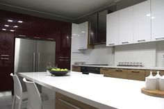 Glossy rich red cabinets wall houses the refrigerator adding spirit to this airy kitchen designed by decades+