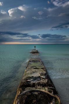 Man fishing at the end of a pier made of rock in Holbox Island, Mexico.