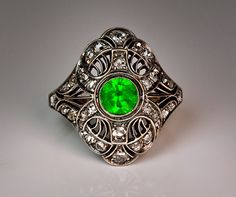 A Vintage Art Deco Demantoid and Diamond Ring  Moscow, circa 1930  An elaborate openwork silver and gold ring features a very fine vivid green Russian demantoid garnet in a surrounding of 34 rose cut diamonds.  The demantoid is 5.6 x 3.4 mm, approximately 0.75 ct.  Estimated total diamond weight - 0.55 ct.