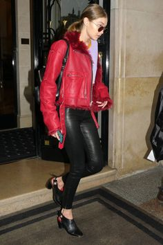 In a red fur-lined leather jacket, purple tee, black leather skinny jeans by J Brand, heeled mules, a black leather backpack and rounded sunglasses while out in Paris.