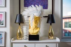 Champagne bottle lamps and a sculpture with a headdress. Love this house.
