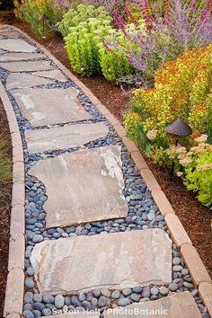 Um caminho forrado de tijolo com trampolins e enchimento de cascalho |  Áreas ao ar livre