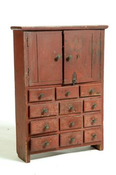 American, 19th century, pine. Two plank doors over twelve small drawers. Old red paint