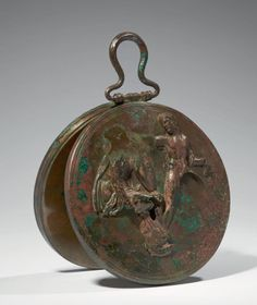 RARE MIRROR BOX. The lid is decorated with a wall depicting a young satyr naked face to the goddess Athena seated, draped, holding his shield (probable Athena and Marsyas representation). The interior has a radiant decoration on silver background. Handle removable suspension. Bronze and silver. Gaps. Greek Art, fourth century BC.
