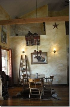 Beautiful light tan dining room with rustic western accents. The saddle tops off the room. | Stylish Western Home Decorating.