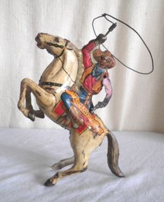 Antique, Metal,  cowboy wind up toy.  Lassoo Twirls, Horses Front Legs Move.  Very Cool.