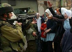 Israeli soldier pointing his gun to Palestinian girls going their way to school .