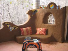 """A cob bench and """"Wave"""" sculpture in Mexico. A niced stain glass window at the top."""