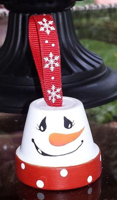 This is a handmade ornament. It is a small clay pot painted to resemble a snow man. A snow flake ribbon adorns the top as the hanger. This