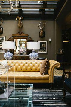 das gelbe Leder Sofa und die Tierköpfe an der Wand sagen viel über dem Besitzer