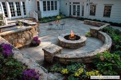 Glowing patio wit outdoor firepit and ouval seats and doors and small garden and stone ground and chairs