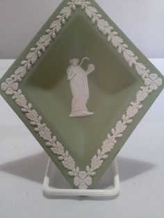 A lovely collectable diamond shape pin tray from Wedgwood. This is in the green jasperware ware with white bas relief. Leaf and flower garlands round the edges.It measures 15 by 11 centimetres and is in lovely condition. Toast Rack, Leaf Border, Breakfast Set, Ivy Leaf, Flower Spray, Flower Garlands, Wedgwood, Diamond Shapes, Pale Pink