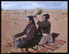 """Navajo Barber Shop"" –  An Navajo Indian women dresses her husband's hair as they sit on the desert floor in the open-air-living room. The man holds the string with which the women will bind his locks. Doing each others hair is a sign of affection for each other.  Photo and Caption by Josef Muench."