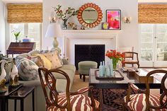 This comfy living room demonstrates the power of mixing patterns and styles–from faux-zebra print to ikat to seagrass, it all comes together with a festive flair! - Traditional Home®  Photo: Grey Crawford Design: Ruthie Sommers