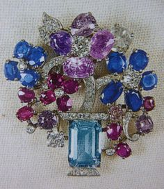 The Queen`s Floral Flowers in a Vase brooch, it features a fairly large aquamarine with a diamond base, & what looks like flowers in a vase made from sapphires, rubies & amethysts with diamond centres & stalks.