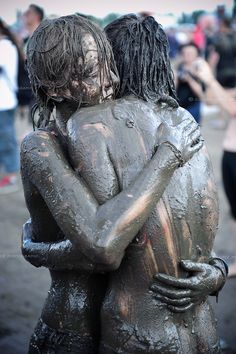 Couple huging covered in mud at the Przystanek Woodstock - Europes largest open air festival in Kostrzyn, Poland