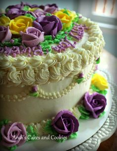 "Birthday cake or any occasion with purple and yellow buttercream roses, 9"" round vanilla cake with chocolate mousse filling."