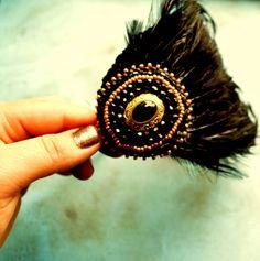 Black Wings  velká luxuní čelenka vytvořená kombinací korálkové výšivky a velké péřové podložky v černozlaté barvě. Obojí k sobě barevně ladí.. výšivka je přišita k péřovému základu, celá část je slepena s pevnou částí vysokogramážního pevného filcu a brokátu přes čelenku, sešita a začištěna.. základ na čelenku je v měděné barvě a má ...