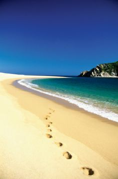 Footprints in the sand on Cacaluta Bay beach in Huatulco, Mexico