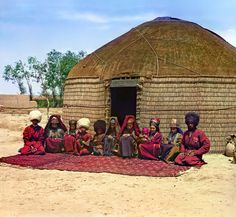 Sergey Mikhaylovich Prokudin-Gorsky:  Tekin with his family (group of eleven adults and children, seated on a rug, in front of a yurt). Russia, Transcaspian Region, Merv uyezd (district), Bairam-Ali area, 1911