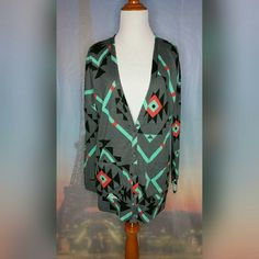 GRAY TRIBAL PRINT CARDIGAN Size Small. Gray/black/turquoise/orange. Tribal print. Two pockets. Button down. Long sleeve. Dropped shoulder. 95% Polyester/5% Spandex. Excellent condition. No tears or stains. Hits mid thigh. Nollie Tops Button Down Shirts