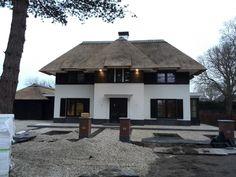 gestuct huis met zwarte potdeksel planken. Rieten dak vanaf de tweede verdieping met plat dak. Voorkant.