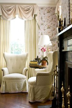 traditional European livng room. cream bell swags (available DesignNashville shipping to you) tufted wing chairs, chinoisserie wall covering. dark stained floors and fireplace