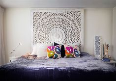 Bohemian bedroom - purple velvet bed spread, hand carved white wash head board & eclectic knick knacks. Delightfully homely.