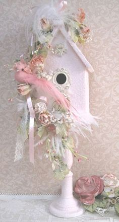 Wooden bird house on a spindle painted in a pale pink and covered in crystal glitz.