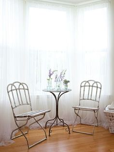 Tea with your best friend as relaxing as sitting outdoors: a flea market cafe chair pulled up to a side table loaded with cut blossoms. Sheer curtains catch breezes from the window.
