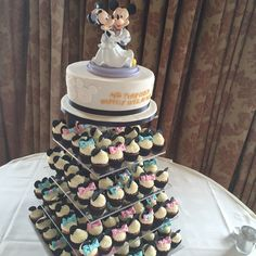 "A Disney themed wedding tower. Single tier cake appliquéd with Minnie & Micky and hand piped ""and they lived happily ever after"". Mini cupcakes decorated with Mickey Mouse ears and Minnie Mouse ears & bows. Topper supplied by couple. www.kellylou.com"