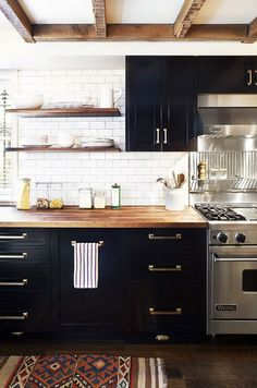 Black cupboards, wooden counter tops, wooden shelves, steel oven and stove top, tribal print rug, brick wall, wooden floor