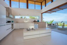 12 Inspirational Examples Of Letterbox Windows In Kitchens // While the kitchen of this villa didn't necessarily need the light from the letterbox window, it acts as an art piece, providing views of the blue sky and green palm leaves.