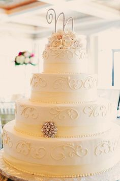 Scroll-y creamy flowery top wedding cake - either change or totally omit the brooch & use fresh flowers