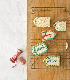 To create these confectionery name tags, follow our recipe for sugar cookie dough. Form the cookies with a tag-shaped cutter, then use a plastic straw to punch a hole in the pointed end of each treat before baking. Customize each cookie by piping names and decorative edging with icing.  Recipes: Sugar Cookie Dough and Royal Icing   - CountryLiving.com